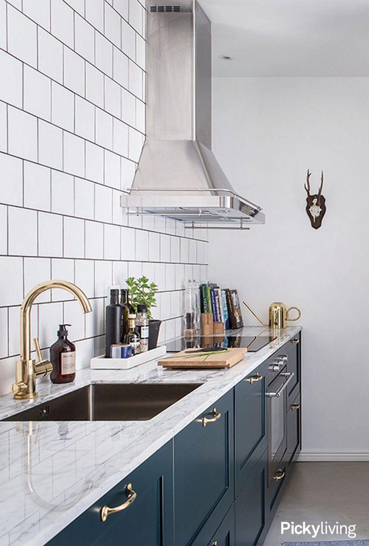 Mörblå, mässing och marmor i detta underbara kök