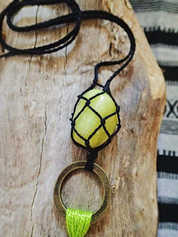 A gorgeous pale lime green Serpentine gemstone features as the centrepiece of this gypsy necklace. The crystal is nestled in a hand knotted cotton macrame pouch, and highlighted by a matching tassel charm. Measuring approximately 33 inches (84cm) in total length, the chain is 26 inches (66cm) around making it easy to slip on over your head.