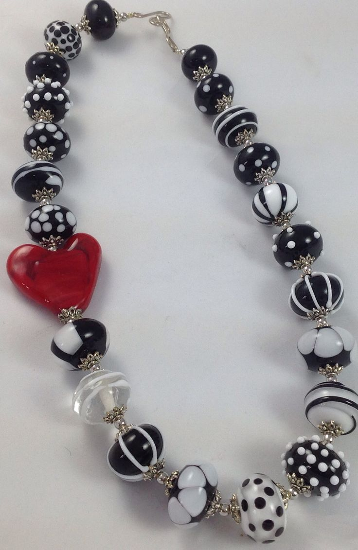 A very stylish Necklace of Black and White Beads with a sumptuous Red Heart Accent. A Sterling Silver Hand Made Clasp for closure.