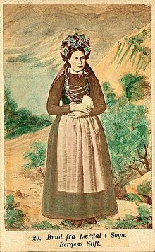 """Brudedrakt med snørelenke, fra Lærdal omkring 1870. Bildet kommer fra serien """"Norske Nationaldragter"""" (nr.20) fotografert av Marcus Selmer (1819-1900), Bergen. Billedsamlingen Norsk Folkemuseum."""