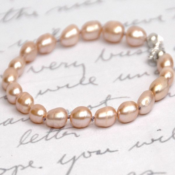 Beautifully dainty and petite, this adorable freshwater pearl bracelet will soon become a most cherished design.  Each lustrous freshwater pearl is a translucent shade of peach and oval in shape. Each pearl is individually hand knotted with rose pink silk.