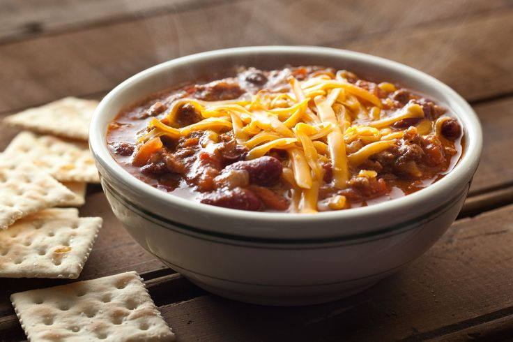 A tasty chili recipe made in a slow cooker with a mixture of ground beef, onion, garlic, bell pepper, chili powder, cumin, tomato, beans, and jalapeños.