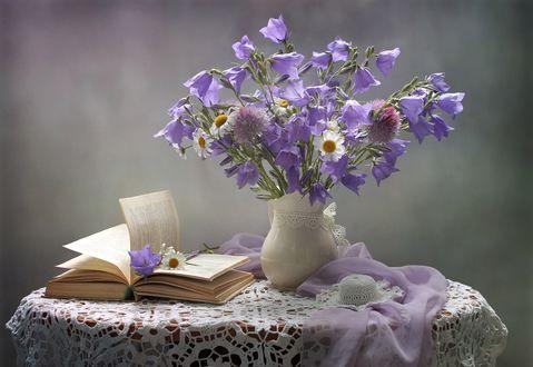 Букет из колокольчиков, ромашек и клевера стоит на столе, покрытом кружевной скатертью, рядом раскрытая книга, цветы и вуаль