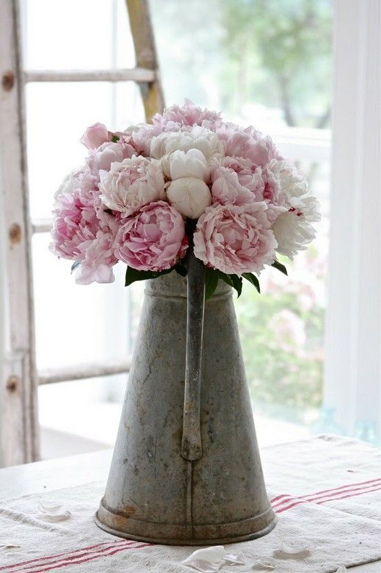 fresh picked flowers pink peonies in a rustic water pitcher