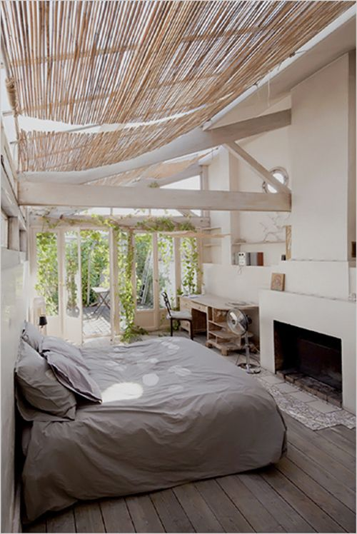 Master bedroom opens to a terrace and has a skylight that spans the ceiling, covered with retractable straw shades.