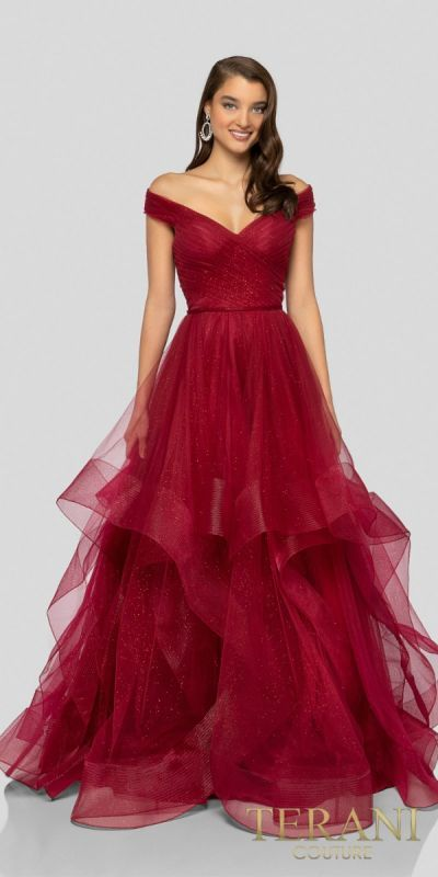 f2ba348b95f Be the belle of the ball in the enchanting Off the Shoulder Pleated Glitter  Tulle Ballgown by Terani Couture. This dreamy ensemble features a v-shape  ...