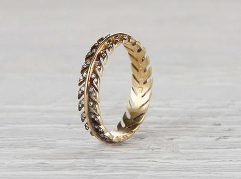Made in 18k yellow gold and accented with single cut diamonds. Band is 4.28mm wide. Made to order. Please allow 3-4 weeks. Reminiscent of a feather, this light as air band is as delicate as it is exquisitely crafted. Accented with blackened edges, this band is beautiful alongside other rings, but also stands out on its own.  We only select diamonds that are antique or repurposed with a focus on old-european, old-mine and single-cut. Always forged with recycled metals. All of our jewelry is…
