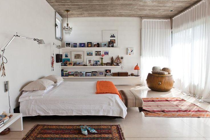 Dormitorio moderno con techo de hormigón que se suaviza con el detalle del tambor de madera y almohadones, y las alfombras en textiles naturales.