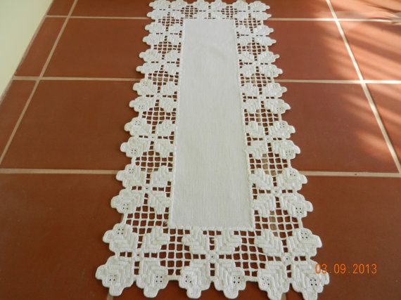 Ivory colored linen table runner with white cut-work edging. The thread used in edging looks and feels like cotton sheen. Hardanger embroidered edge.    19 long, 8 wide. There is a tiny light coffee colored spot on the tip of one of the edging picots, which is shown is the 3rd photo. After photographing, I dabbed at it with a damp white towel and mild soap and it did disperse quite a bit. It may come out completely with a good soak. Other than that, this pretty runner is in pristine like-new…