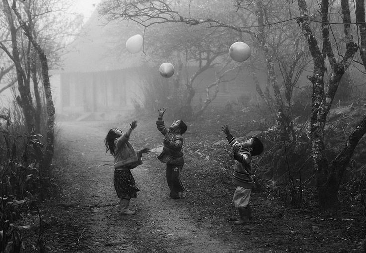 [National Geographic Traveler Photo Contest 2012]  Second Place Winner: My Balloon  H'mong children play with their balloons on a foggy day in Moc Chau, Ha Giang province, Vietnam; photographed January 2012.  Photo and caption by Vo Anh Kiet.        http://travel.nationalgeographic.com/travel/traveler-magazine/photo-contest/2012/entries/gallery/winners-winners/#/1