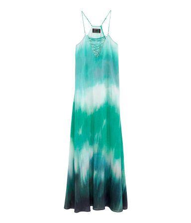 Een uitlopende maxi-jurk van fijne, geweven kwaliteit met een geprint dessin. De jurk heeft smalle, verstelbare schouderbandjes, een decoratieve rijgsluiting bovenaan en een racerback. Ongevoerd. De jurk is deels gemaakt van Tencel® lyocell.