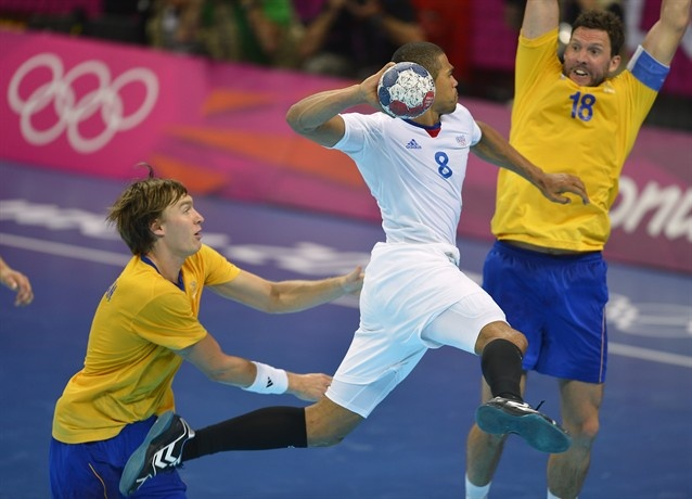France's centreback Daniel Narcisse (C) shoots the ball during the men's gold medal handball match between Sweden and France.