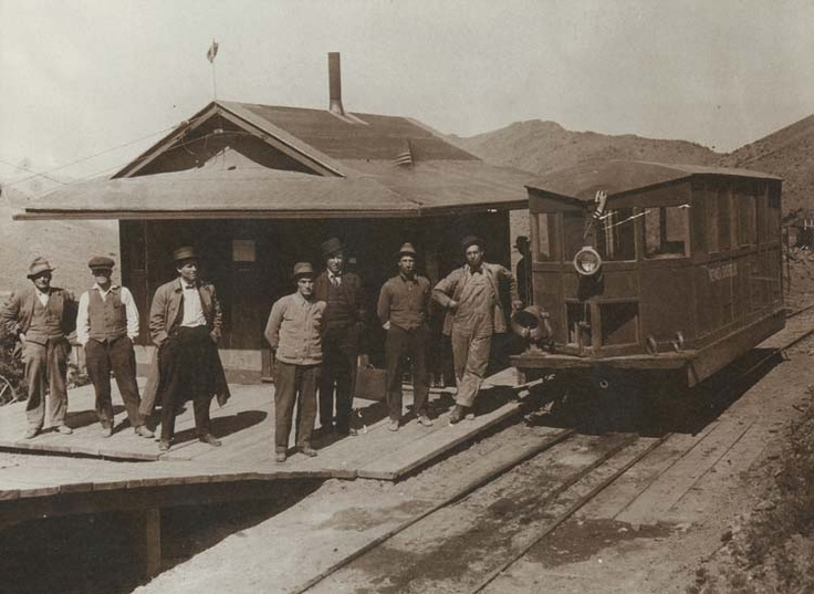 Engineer, Owen F. Oviatt, (far right) leans on Mike, a locomotive that provided passenger service between Rochester and Lower Rochester, Nevada, about 1915. Mike consisted of a Winston automobile frame and motor built onto two light railtrucks. The Cab was handmade.Passenger, Lights Railings, Automobiles Frames, Motors Built, Lower Rochester, Nevada Ghosts, Lights Railtruck, Aboard Training, Mike Consistency