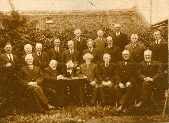 """De Brandwaarborgmaatschappij """"Tietjerksteradiel"""" vierde dezer dagen (10-6-1927) haar 26-jarig bestaan.  Van links naar rechts (zittende) de heeren:  T.W. Oostenbrug, J. Falkena (boekhouder), TJ. Haisma (voorzitter), P.J. Bosma, G.F. Schrapsma en A.W. Veenstra.  Van links naar rechts (staande) de heeren: J.Hamersma (bode), S.A. Visser, A.G. Riemersma,  K.D. de Boer, L.F. Antoeides, M Visser, P.T. Oosterhof, P.Kramer, A.D. de boer, B.Dijkstra (bode), J.F. Bottinga en B.J. van der Meulen"""