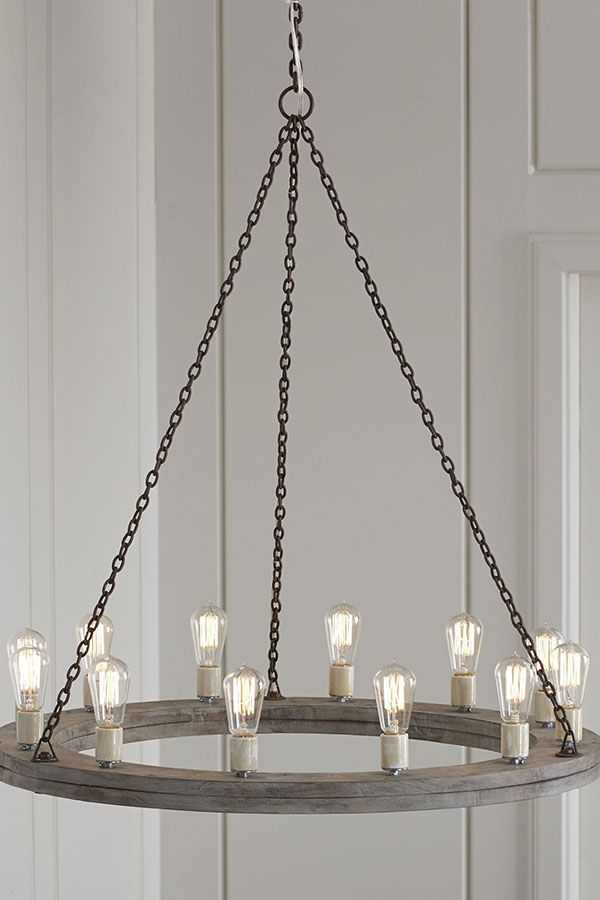 A Ring Of Grey Finished Mango Wood Hangs Down From Weathered Iron Chain To Cast Rustic Glow Over Dining Table Or Kitchen Island