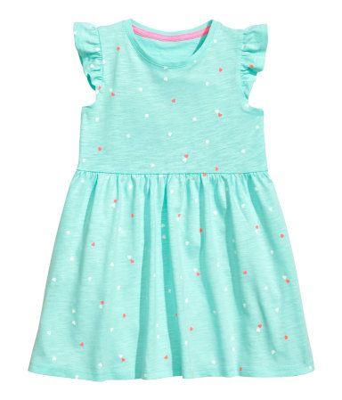 Mintgrön/Hjärtan. CONSCIOUS. En klänning i ekologisk bomullstrikå med tryckt mönster. Klänningen har kort volangärm och är avskuren i midjan med rynkad kjol