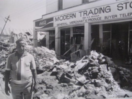 R.R. Bhana in front of his wrecked shop.