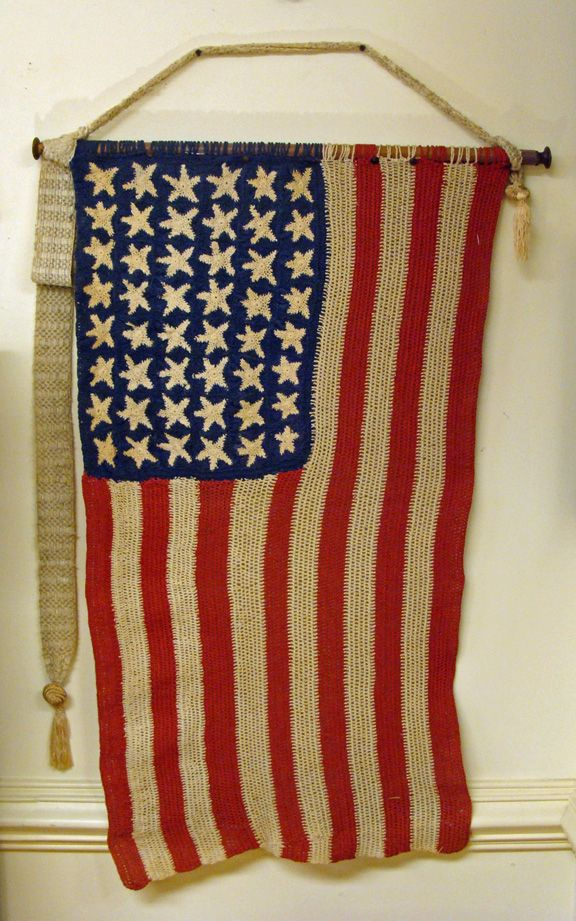 """This is a hand-crocheted cotton line 48 star US flag probably made soon after Arizona was admitted to the Union in 1912. The flag is in excellent condition with no rips, tears or stains. Color is vibrant. It's a wonderful example of Americana folk art from the flag itself to the embellished broom handle flag pole, and crocheted cord and tassel. The flag measures approximately 23"""" x 39"""" and 28 1/2"""" X 50"""" overall including the wooden pole and crocheted hanger."""