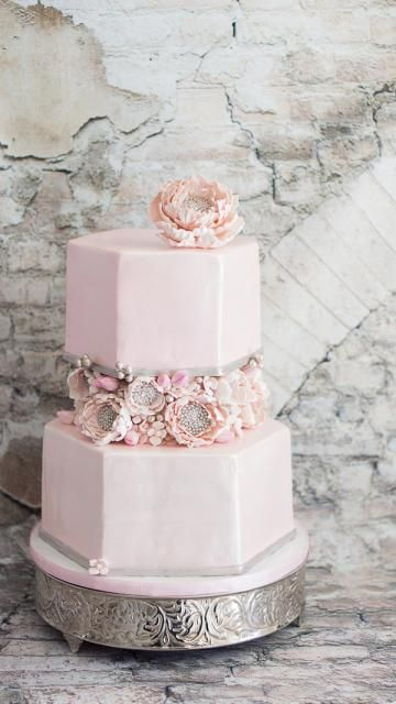 Hexagonal shaped pink fondant wedding cake with pink sugar flowers