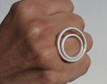Deze ring lijkt te zweven over de hand. Haar rustige is groot maar licht en gemakkelijk te dragen. De ring is gemaakt van 2mm vierkante draad in sterling zilver. Het wordt geweven met de randen gepolijst voor een mooi contrast. De diameter van de cirkels zijn ca. 24 mm en 16 mm. De ring getoond in ring grootte 12 EU of 6 ons is, maar in elk formaat kan worden gemaakt in 3 dagen. Laat de ringmaat in bericht aan de verkoper wanneer u het maken van de aankoop! Als al mijn items zijn voorz...