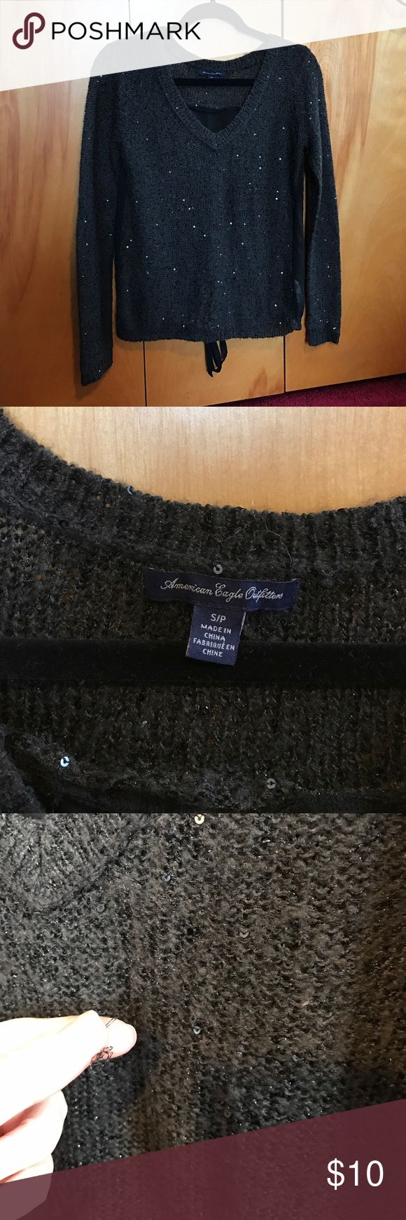 American Eagle Shimmering Sweater American Eagle sweater, size small. The sweater is dark grey and has sequins and glitter throughout the sweater that makes it shimmer and sparkle! The sweater may catch easily to jewelry so be careful. The back of the sweater is beautiful and it has sheer material that ties on the bottom as pictured. The sweater has a few pulls in it as pictured., American Eagle Outfitters Sweaters