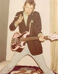 The Nipple Erectors June & August of 1977 Early pic  Shanne's bedsit in Stavordale Road, Drayton Park London N5. Drummer Arcan Vendetta posing with a cigarette holder and Ms Shanne Bradley's Bass
