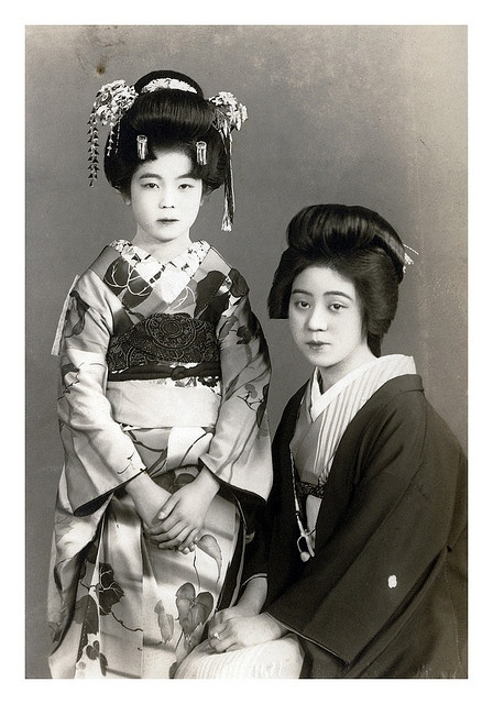 "Geisha 1910 - a maiko and her older sister sit for a photo. The maiko who is standing is making her debut, the two silver flutters are signal to that. Onesan means ""older sister"", they weren't actually sisters. The older one was a mentor to the younger apprentice and taught her everything she needded to know."
