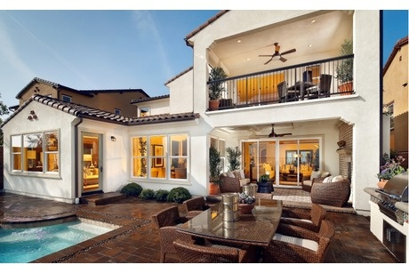 A covered patio and balcony overlook an inviting pool; glistening tile around the pool echoes the roof tile. Residence 2 by Standard Pacific Homes. Montserrat At Blackstone. Brea, CA.