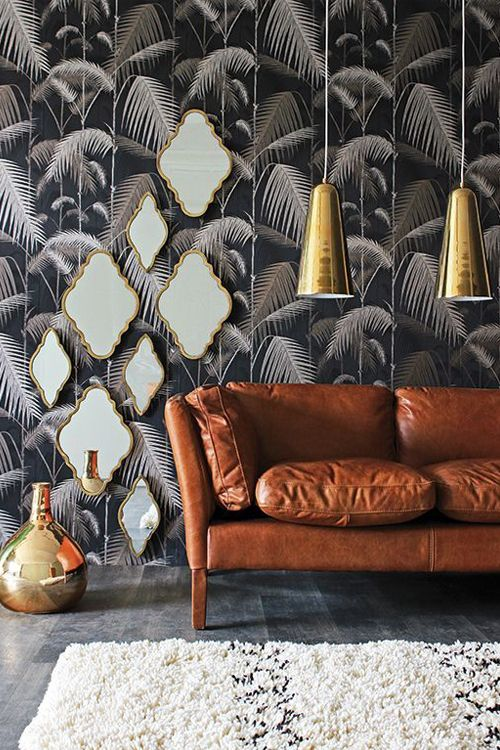 Tropical leaves with shining golden decorations and a brown couch