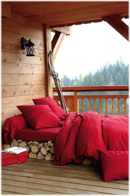 I want to sleep here! Red bed coverings, wood walls and a view.