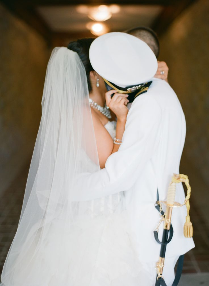 My groom a US Navy Officer in his dress whites and me in my Lazaro wedding dress and cathedral length veil stealing a kiss behind his hat (cover).