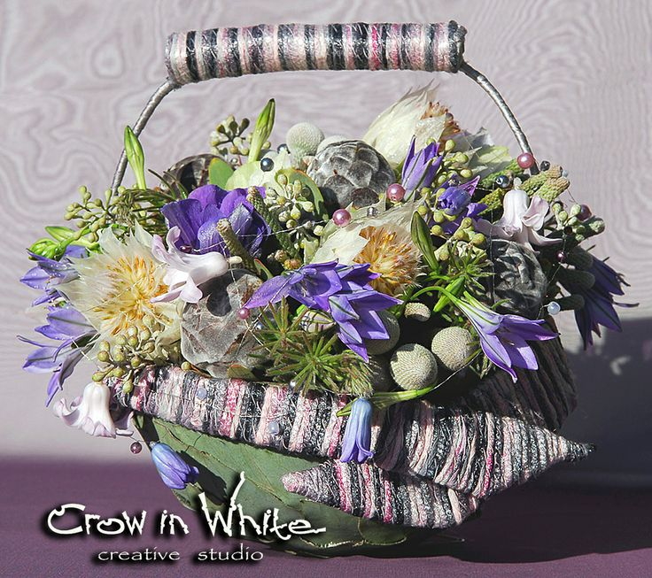 Bride or bridesmaid bouquet in elegant basket shape. Light purple, grey and white flowers connected with yarn.