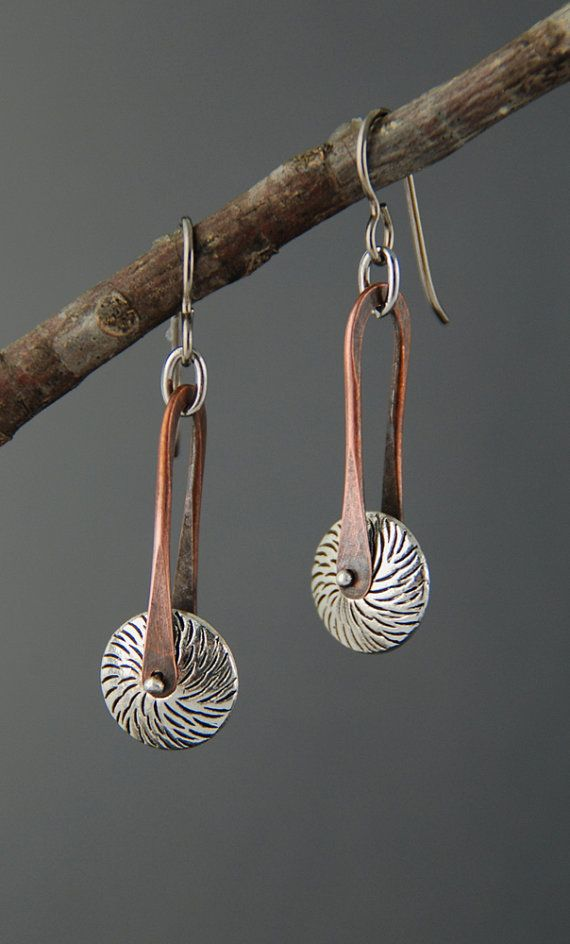 A lightweight pewter bead, reminiscent of a spur, is pinned into place with a silver rivet, spinning freely inside a hand forged stirrup shape. Earrings