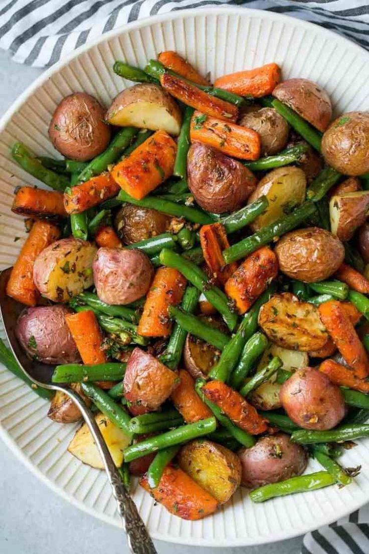 """Vegan Garlic Herb Roasted Potatoes, Carrots and Green Beans // Keep the side dish simple with this easy roasted potato, carrot and green bean mix. The mouthwatering garlic and herb """"dressing"""" makes this recipe exciting and flavorful. 
