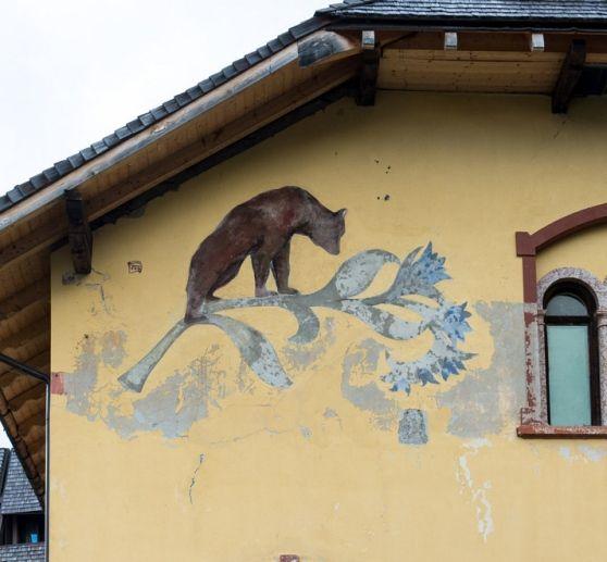 """Il simbolo di Madonna di Campiglio: l'orso bruno, adagiato sullo stelo di un raponzolo di roccia. Il disegno originale fa parte dei dipinti realizzati dal pittore Gottfried Hofer per decorare, alla fine del XIX secolo, il salone delle feste dell'hotel """"Des Alpes"""", il Salone Hofer (prima del restauro)"""