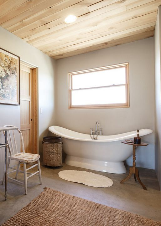 The Signature Hardware cast iron tub in this cozy bathroom pairs perfectly with rustic decor and neutral colors. Try this style in your new home or for your home renovation for a simple yet luxurious look.