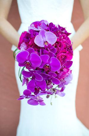 Vibrant purple and magenta bridal bouquet - phalaenopsis orchids, garden roses, dendrobium orchids.