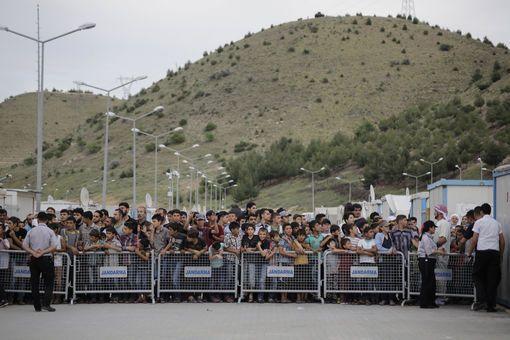 Des réfugiés attendent la venue de la chancelière allemande Angela Merkel, lors de sa visite d'un camp de réfugiés à Gaziantep, près de la frontière turco-syrienne, le 23 avril 2016