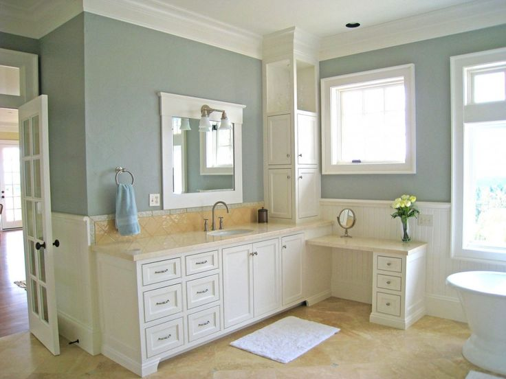 calm wall paint color scheme of bathroom with tall white wooden corner storage cabinet built in
