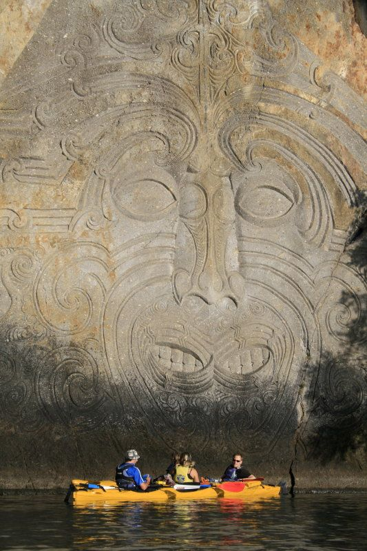 Maori Carving in Rockside, Lake Taupo, New Zealand - The spiritual & cultural beauty of the Maori rock carvings at Mine Bay on Lake Taupo are over 10 metres high & tower over the deep waters of Lake Taupo.