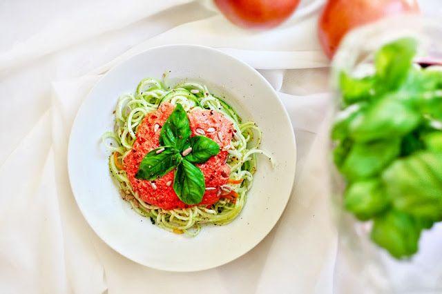 Składniki (2-3 porcje): 2 małe lub 1 duża cukinia + 1 mała marchewka (opcjonalnie) 2 duże pomidory malinowe, obrane ze skórek z miare możliwości (bez spażania) 100g nerkowców, namoczonych uprzednio na noc lub przynajmniej przez kilka godzin garść ziaren słonecznika 1 ząbek czosnku, przecisnięty przez praskę lub drobno pokrojony przyprawy: świeżomielony pieprz, sól, kolendra, bazylia, oregano 1 łyżeczka aromatycznej oliwy z oliwek świeża bazylia, do dekoracji
