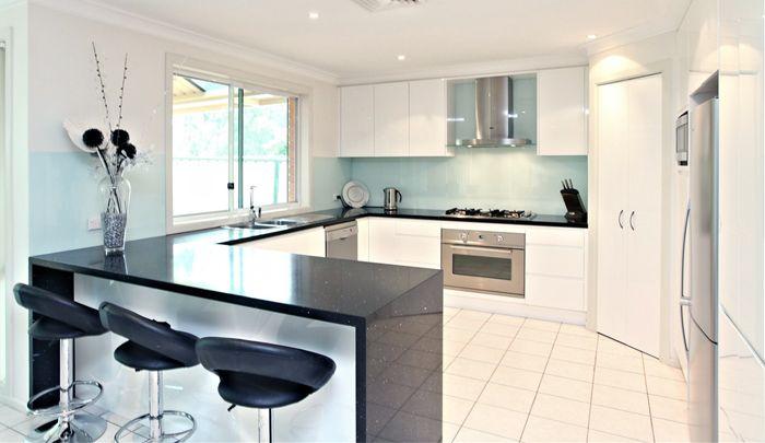 Kitchen glossy white cabinets black quartz bench top for Black white and blue kitchen ideas