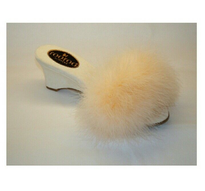 The clasic foofoo mule slipper has a rich fluffy cream sheepskin top. With the classic scooped wedge heel, it is elegant, classy & unique.  The material is a beautiful rich velvet,  &the fact that its hand made by a true craftsman makes it to the perfect slipper.