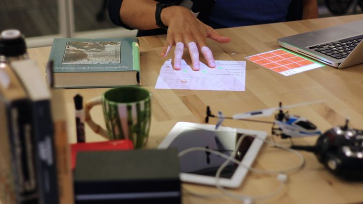 A prototype device uses a small projector, a depth sensor, and a computer to project multi-touch displays onto any surface.