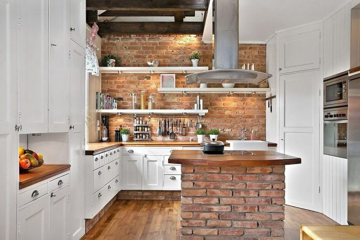 Cozy duplex kitchen in Gothenburg Sweden features a brick cooking island and dark exposed joists to contrast with the white cabinetry. [768  512]