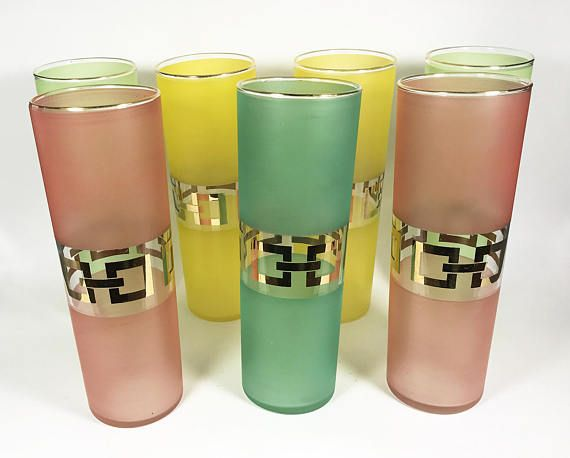 Mid-century frosted tall drinking glasses with gold gilt key motif and trim. The set of 7 glasses features 2 yellow, 2 light green, 2 reddish-pink and 1 bright green. We have seen a pitcher and juice glasses with the same motif and coloring that were attributed to Corning Glass Works however we cannot confirm if they are the manufacturer of these glasses. The glasses are in wonderful condition; no chips, cracks or repairs. There is light wear to the gold rim and key motif, refer to the…