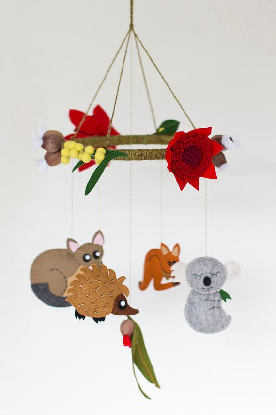 This Australian animal baby mobile features a kangaroo, koala, brush-tailed possum and echidna hanging under a ring of Australian native flowers. Created by BabesInTheWoodsShop on Etsy