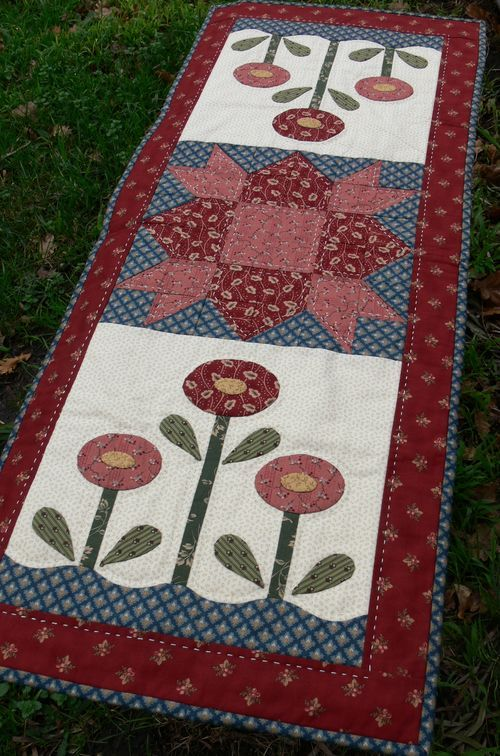 Country blooms. like the applique with pieced block. add petals. different center block but like the idea. a lot!