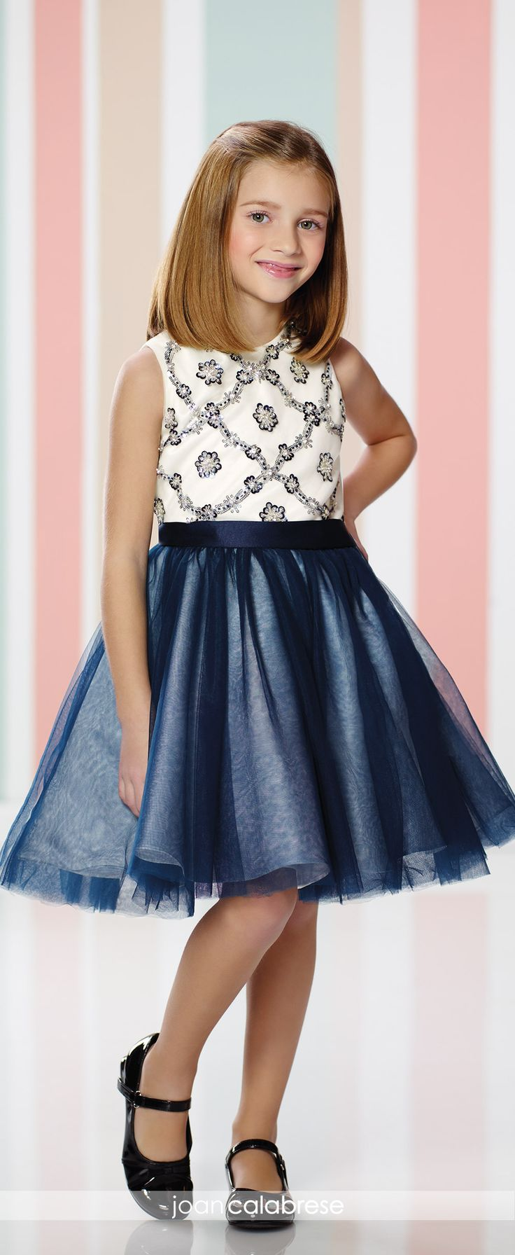 Joan Calabrese for Mon Cheri - 216317 - Sleeveless satin and tulle knee-length full A-line dress with high jewel neckline, tulle overlay bodice with crisscross sequin trim, satin waistband, double layered tulle overlay skirt.Sizes: 2 – 14Color: Ivory/Navy Blue