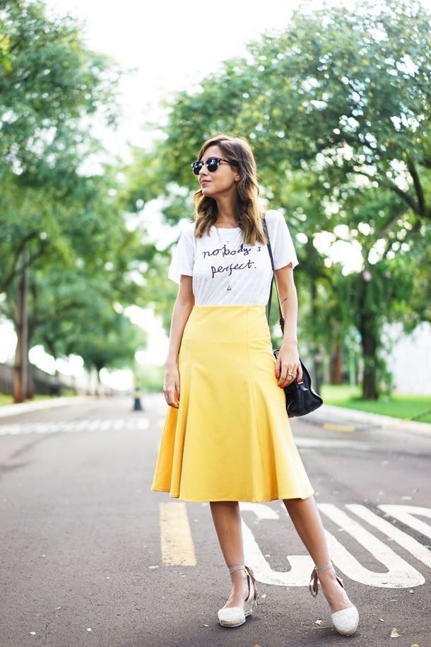 Luisa Accorsi, street style em look com saia mídi amarela, camiseta e espadrille.